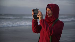 Løvetannmamma - Woman taking a picture of the beach