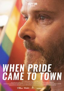 When pride came to town - Man crying beside the LGTBQ flag